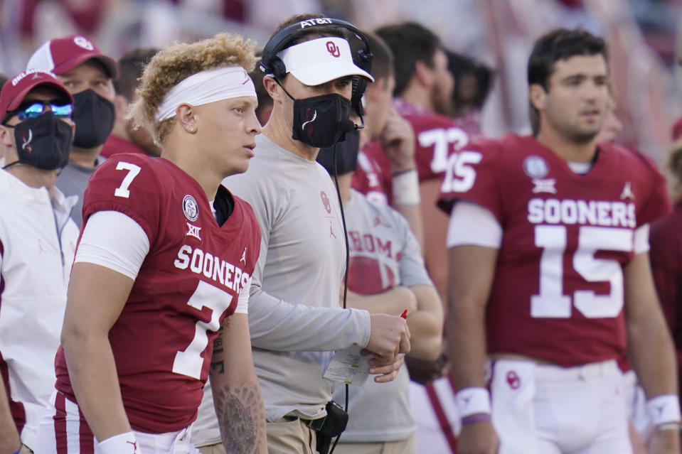 Oklahoma head coach Lincoln Riley talks with Oklahoma quarterback Spencer Rattler (7) during an NCAA college football game against Kansas in Norman, Okla., Saturday, Nov. 7, 2020. (AP Photo/Sue Ogrocki)