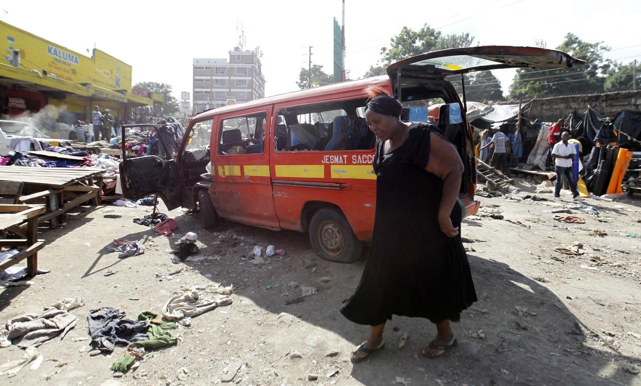 A woman walks near a damaged vehicle at the scene of a twin explosion at the Gikomba open-air market for second-hand clothes in Kenya's capital Nairobi May 16, 2014. At least four people were killed on Friday in two explosions in Nairobi, the country's National Disaster Operations Centre (NDOC) said. REUTERS/Thomas Mukoya (KENYA - Tags: CIVIL UNREST CRIME LAW TPX IMAGES OF THE DAY)