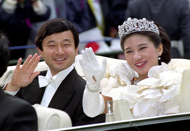 FILE - In this June 9, 1993, file photo, then Crown Prince Naruhito, left, and Crown Princess Masako wave during their wedding parade in Tokyo. Japan is abuzz ahead of a ceremony Tuesday, Oct. 22, 2019, marking Emperor Naruhito's ascension to the Chrysanthemum Throne. It is one of several formal ceremonies for Naruhito, 59, who has been a full-fledged emperor since succeeding in May after the abdication of his father, Akihito.(Kyodo News via AP, File)