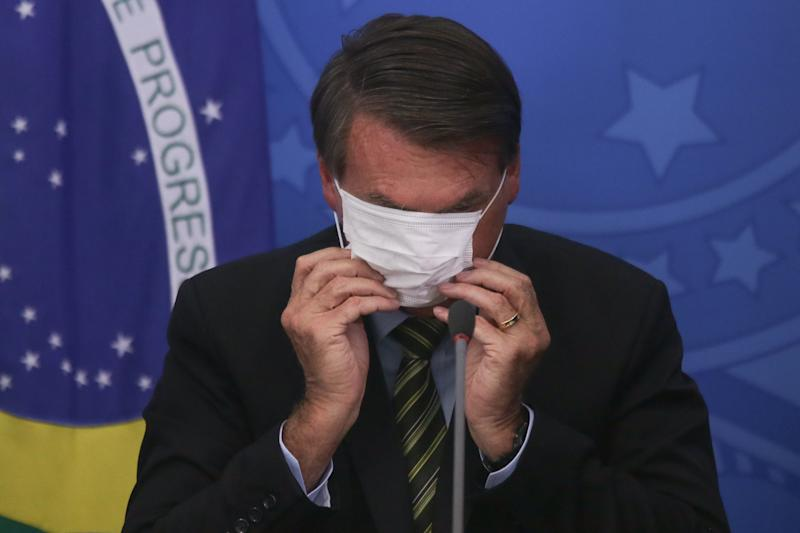BRASILIA, BRAZIL - MARCH 18: President of Brazil Jair Bolsonaro adjusts his protective mask during a press conference regarding government plans and measures about the Coronavirus (COVID-19) Outbreak in Brazil, at the Planalto Palace on March 18, 2020 in Brasilia, Brazil. (Photo by Andre Coelho/Getty Images)
