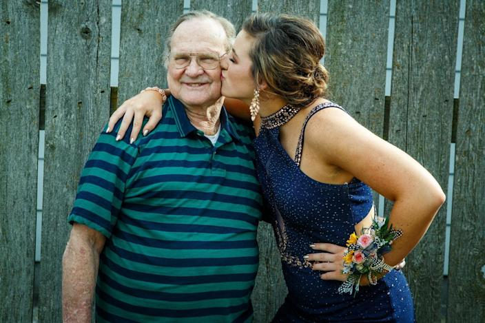 """Edward """"Mac"""" McElhaney beams with pride as his granddaughter, Andrea Charles, kisses him in this undated family photo. McElhaney, 78, died of coronavirus on Oct. 24, 2020, after getting infected in Quinter, Kansas, where he lived."""