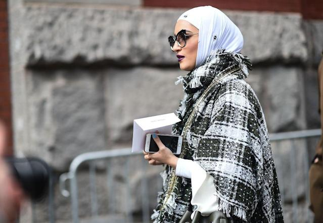 <p>This street-style star pairs her hijab with an elegant plaid scarf, poncho, and crisp white blouse. Add a pair of oversized cat-eye sunglasses and a dark lipstick to achieve this stunning look. (Photo: Getty Images) </p>