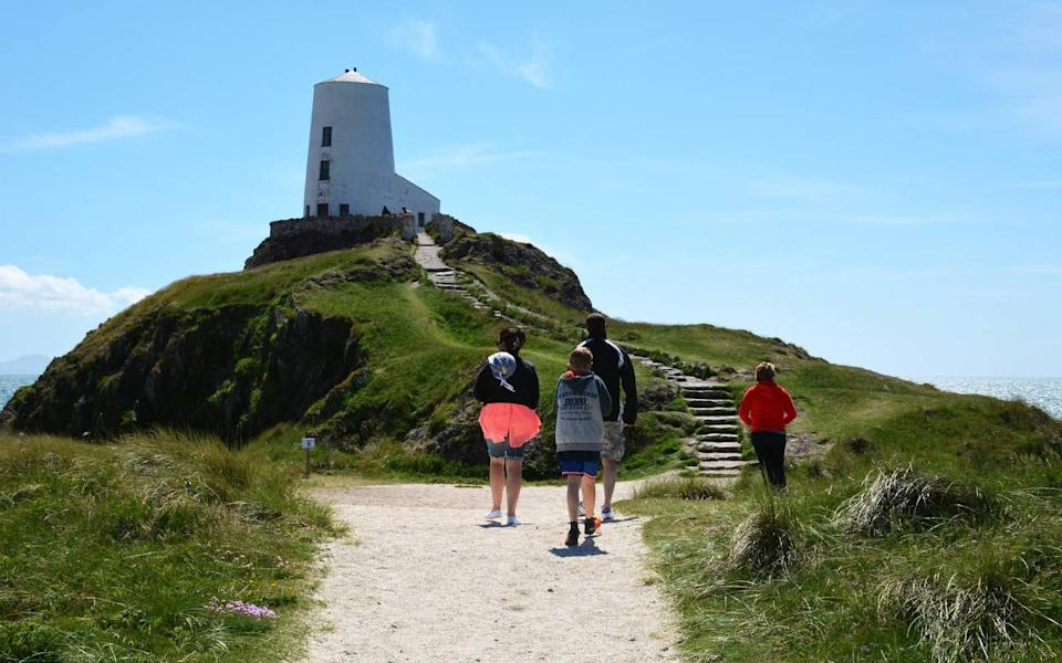 Holiday makers visit Llanddwyn Island Lighthouse (Twr Mawr) of the coast of Anglesey - Tim Snow