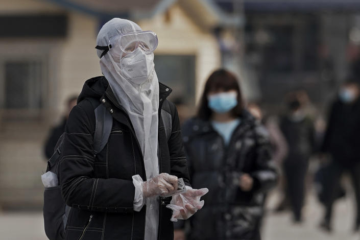 A woman wearing protective gear to help curb the spread of the coronavirus arrives at the railway station in Beijing, Wednesday, Jan. 27, 2021. China has given more than 22 million COVID vaccine shots to date as it carries out a drive ahead of next month's Lunar New Year holiday, health authorities said Wednesday. (AP Photo/Andy Wong)