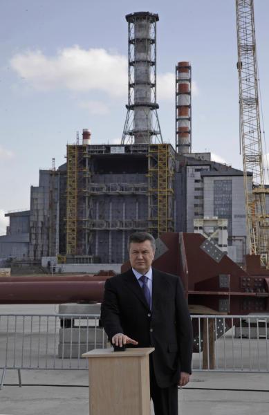 Ukraine's President Viktor Yanukovych pushes a button in a ceremony inaugurating the initial assembly of a gigantic steel-arch to cover the remnants of the exploded reactor of the Chernobyl nuclear power plant in Chernobyl, Ukraine, Thursday, April 26, 2012. Ukraine's president on Thursday thanked the international community for financing the construction of a new, safer shelter over the damaged Chernobyl reactor and urged extreme caution with nuclear energy as Ukrainians, Belarusians and Russians marked the 26th anniversary of the world's worst nuclear disaster. (AP Photo/ Efrem Lukatsky)