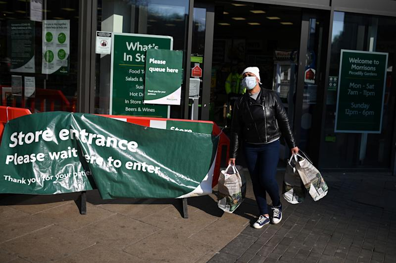 """A shoppers wears a mask as he carries his groceries out of a supermarket in Manchester, north west England on March 27, 2020. - Britain was under lockdown, its population joining around 1.7 billion people around the globe ordered to stay indoors to curb the """"accelerating"""" spread of the coronavirus. (Photo by Oli SCARFF / AFP) (Photo by OLI SCARFF/AFP via Getty Images)"""