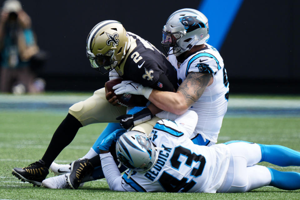 New Orleans Saints quarterback Jameis Winston is sacked by Carolina Panthers defensive end Morgan Fox and outside linebacker Haason Reddick during the first half of an NFL football game Sunday, Sept. 19, 2021, in Charlotte, N.C. (AP Photo/Jacob Kupferman)