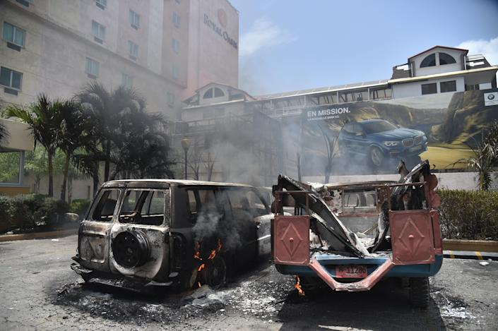 <p>Cars burn in a hotel parking lot in Port-au-Prince after protesters set them on fire on July 7, 2018, during a demonstration against the government's attempt to raise fuel prices. (Photo: Hector Retamal/AFP/Getty Images) </p>