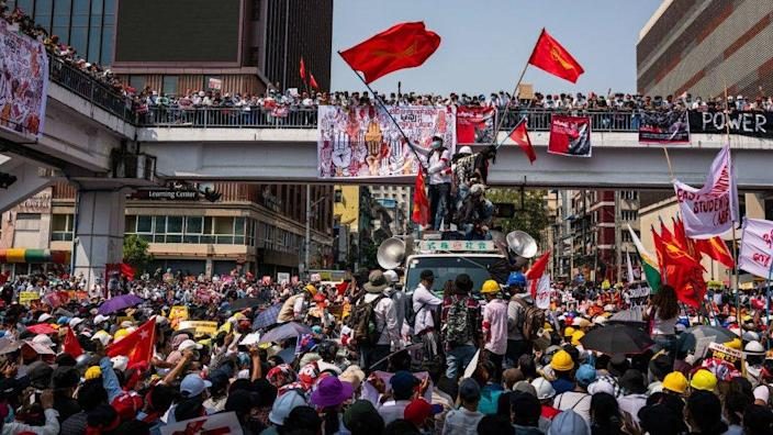 Demonstrators wave National League for Democracy flags at Soli Square on February 22, 2021 in downtown Yangon, Myanmar.