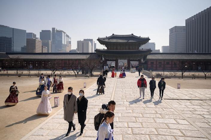 Tourists wearing face masks visit Gyeongbokgung palace in Seoul on February 10, 2020, as a preventative measure after a coronavirus outbreak.