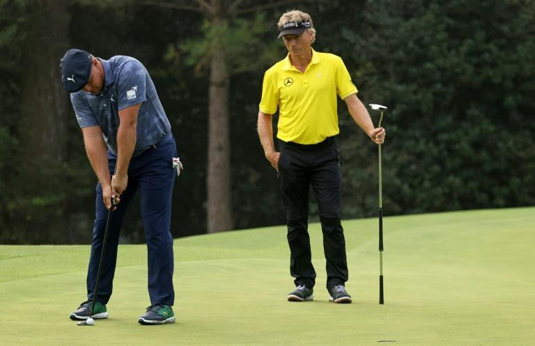 Bryson DeChambeau putts at Augusta as playing partner Bernhard Langer watches