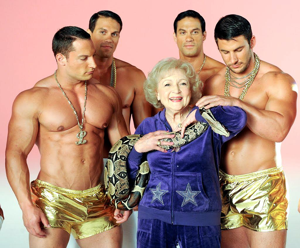 <p>Just a typical day in the life of Betty White: She's hanging around in a purple sweatsuit, with a snake around her neck, while a bunch of dudes in really revealing gold shorts stare at her. (Photo: Getty Images) </p>