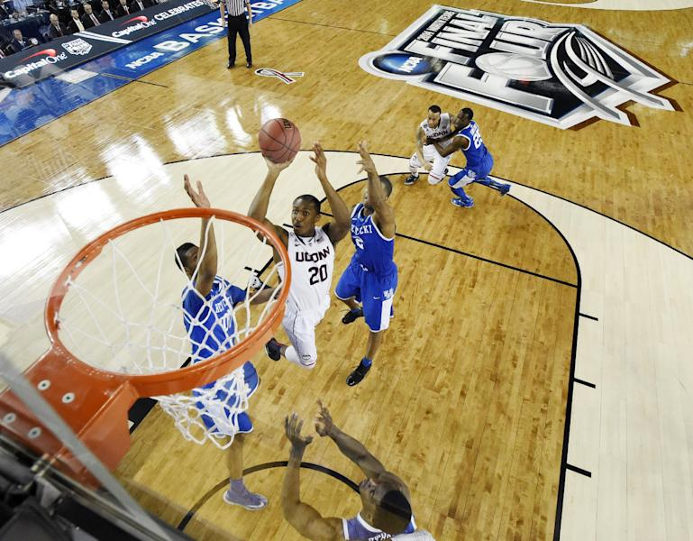 Connecticut guard Lasan Kromah (20) shoots between defenders Kentucky forward Marcus Lee (00) and guard Aaron Harrison (2) during the first half of the NCAA Final Four tournament college basketball championship game Monday, April 7, 2014, in Arlington, Texas. (AP Photo/Chris Steppig, pool)