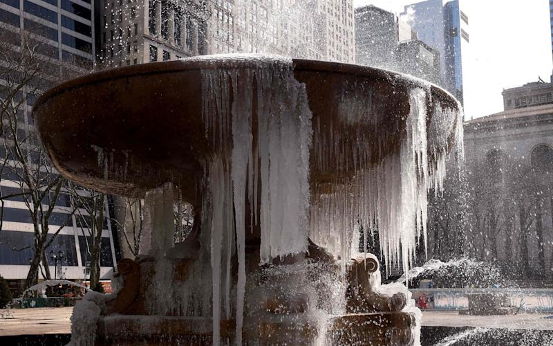The Josephine Shaw Lowell Memorial Fountain in Bryant Park is covered in ice - Credit: AFP