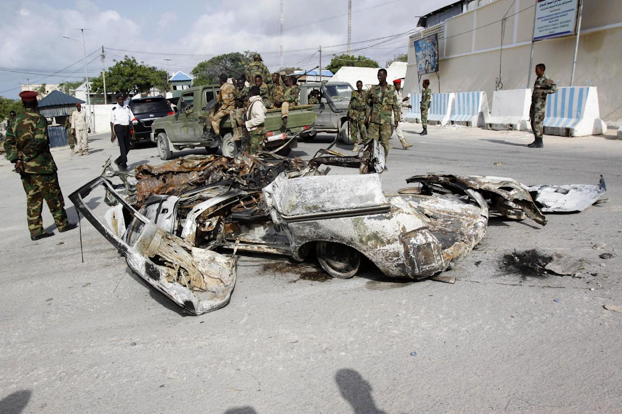 Somali soldiers stand near the wreckage of car bomb that was detonated at the main gate of the presidential palace in Mogadishu, Somalia, Wednesday, July, 9, 2014. Somali troops retook the presidential palace in the capital of Mogadishu after militants forced their way in and exchanged heavy gunfire with troops and guards Tuesday, the latest attack underscoring the threat posed by Islamic extremist group al-Shabab in east Africa. (AP Photo/Farah Abdi Warsameh)