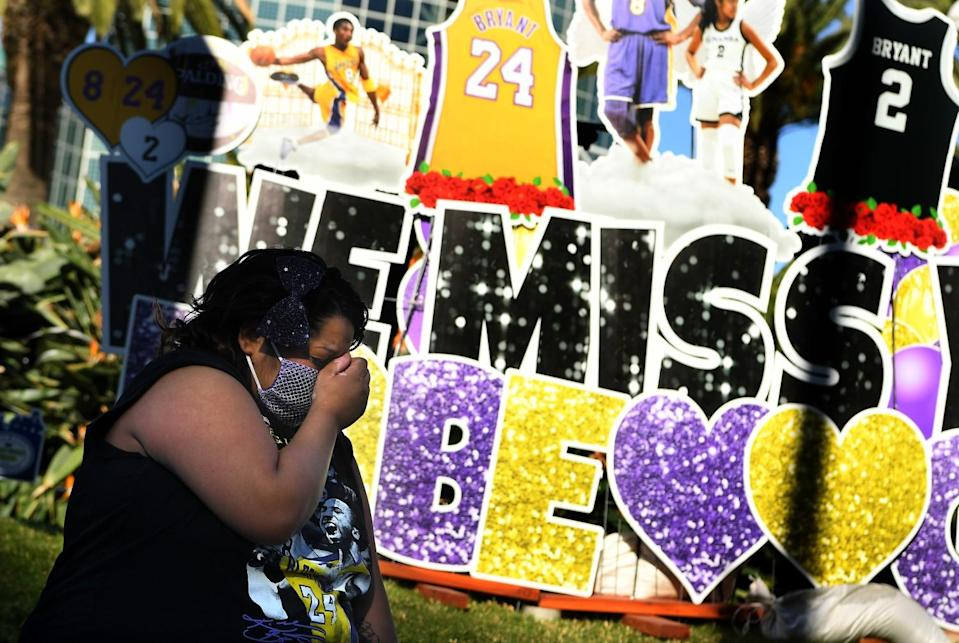 A woman cries in front of a Kobe Bryant mural outside Staples Center.