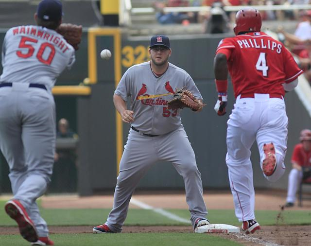 St. Louis Cardinals' Adam Wainwright throws the ball to first baseman Matt Adams to force out the Cincinnati Reds' Brandon Phillips as he bunted to move base runner Shin Soo Choo to second base in the first inning in their baseball game in Cincinnati, Monday Sept. 2, 2013. (AP Photo/Tom Uhlman)