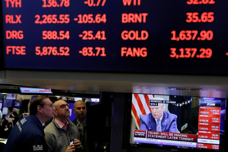 FILE PHOTO: U.S. President Donald Trump is seen on a screen under trading figures during his meeting with bank executives as traders work on the floor of the New York Stock Exchange (NYSE) in New York City