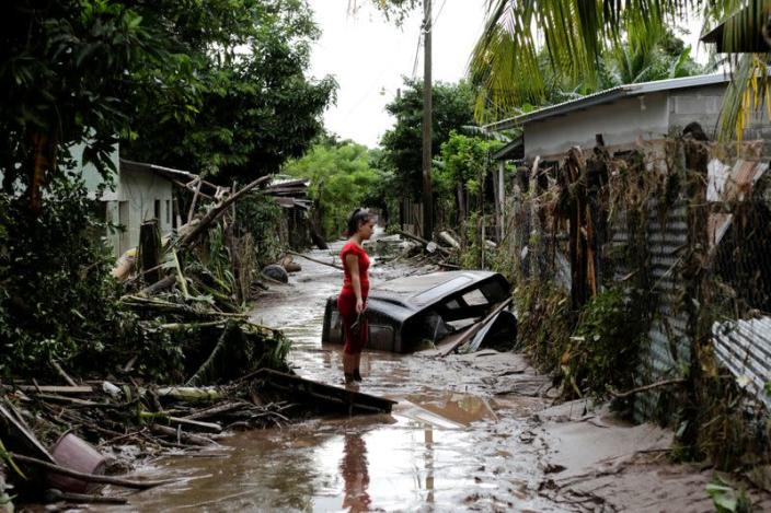A woman stands outside her home damaged due to heavy rains caused by Hurricane Eta, in Pimienta