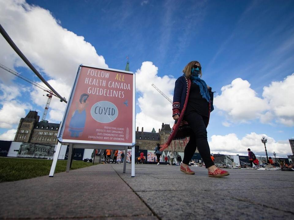 A person in a mask walks past a sign on Parliament Hill urging people to follow Health Canada's COVID-19 guidelines in late September. Health officials in the nation's capital reported 48 new cases of COVID-19 on Saturday.  (Trevor Pritchard/CBC - image credit)