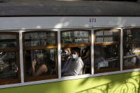 People wearing face masks ride a tram in Lisbon, Friday, June 4, 2021. Britain said Thursday that it is removing Portugal from its list of COVID-safe travel destinations, meaning thousands of U.K. residents currently on vacation there face the prospect of 10 days' quarantine on return. (AP Photo/Armando Franca)