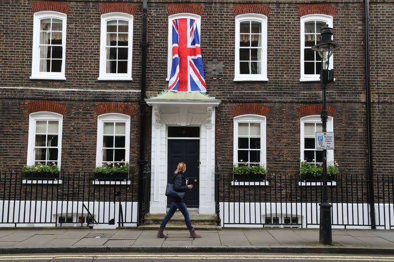 Woman walks past a Union Jack flag hanging on a house in Westminster in London