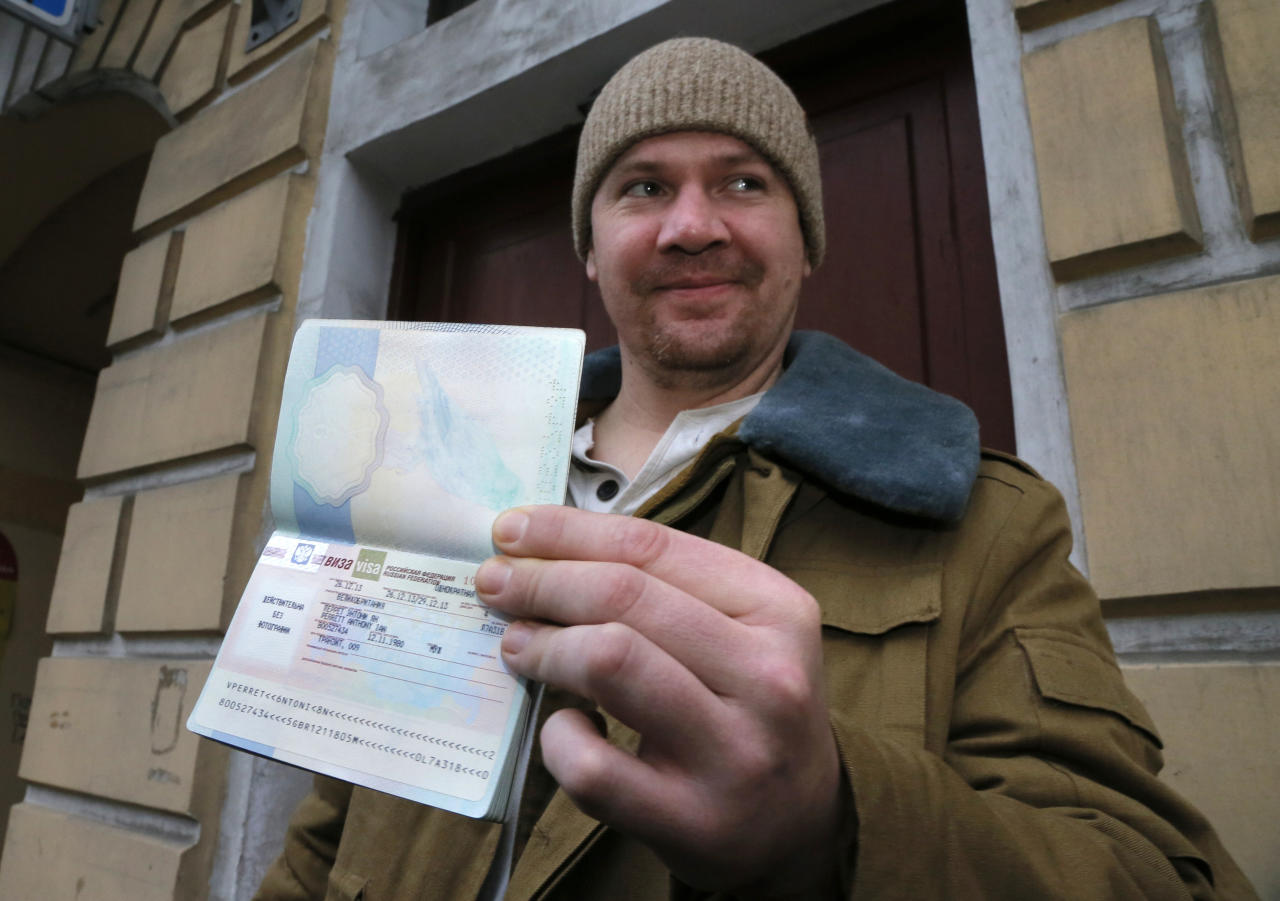 Greenpeace International activist Anthony Perrett of the United Kingdom shows to journalists his passport with permission to leave Russia, near the Federal Migration Service in St. Petersburg, Russia, Thursday, Dec. 26, 2013. Russian investigators have dropped charges against all but one of the 30 crew of a Greenpeace ship, who were accused of hooliganism following a protest outside a Russian oil rig in the Arctic. (AP Photo/Dmitry Lovetsky)