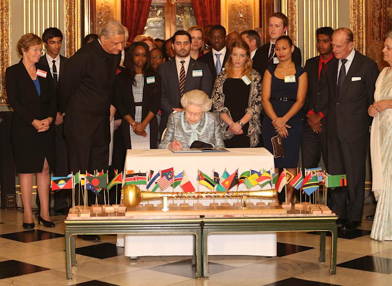 Britain's Queen Elizabeth II, Head of the Commonwealth signs the Commonwealth Charter at a reception at Marlborough House, London, Monday March 11, 2013. The Charter is an historic document which brings together, for the first time in the associations 64-year history, key declarations on Commonwealth principles. (AP Photo/PA, Philip Toscano) UNITED KINGDOM OUT NO SALES NO ARCHIVE