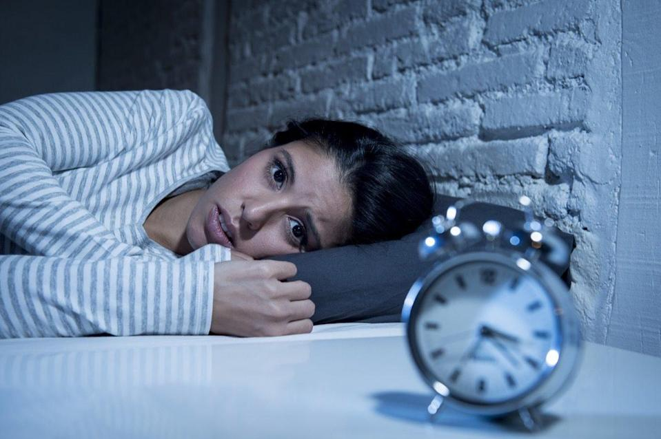 hispanic woman at home bedroom lying in bed late at night trying to sleep suffering insomnia sleeping disorder or scared on nightmares looking sad worried and stressed
