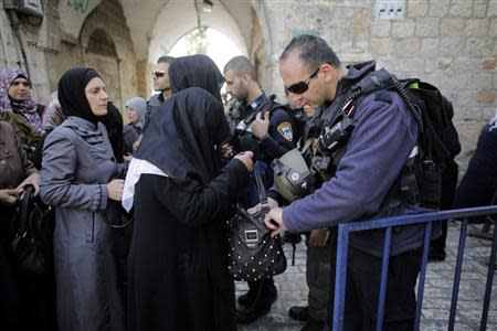 An Israeli policeman checks the bag of a Palestinian woman before she enters the compound which houses al-Aqsa mosque and is known to Muslims as Noble Sanctuary and to Jews as Temple Mount in Jerusalem's Old City April 16, 2014. REUTERS/Ammar Awad