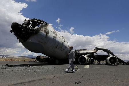 An airport official looks at the wreckage of a Yemeni air force military transport aircraft after it was destroyed by an air strike, at the international airport of Yemen's capital Sanaa