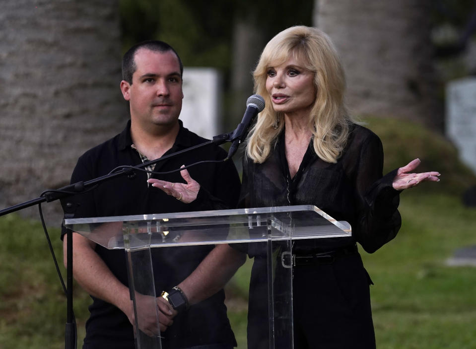 Actress Loni Anderson and her son Quinton Reynolds speak before the unveiling of a memorial sculpture of her former husband and Quinton's father, the late actor Burt Reynolds, at Hollywood Forever Cemetery, Monday, Sept. 20, 2021, in Los Angeles. Reynolds died in 2018 at the age of 82. (AP Photo/Chris Pizzello)
