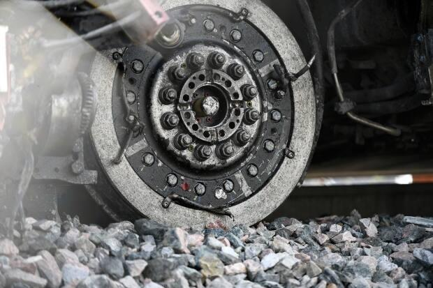 A wheel of a segment of an OC Transpo train is seen off the tracks after it derailed west of Tremblay station. (Justin Tang/The Canadian Press - image credit)