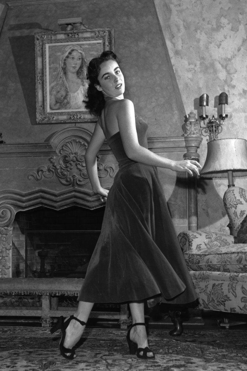 <p>The full skirt and tight bustier of Elizabeth Taylor's dress was the epitome of style in the 1950s, but rather than follow the bright print and pattern trend of the time, the young starlet opted for a simple black fabric. </p>