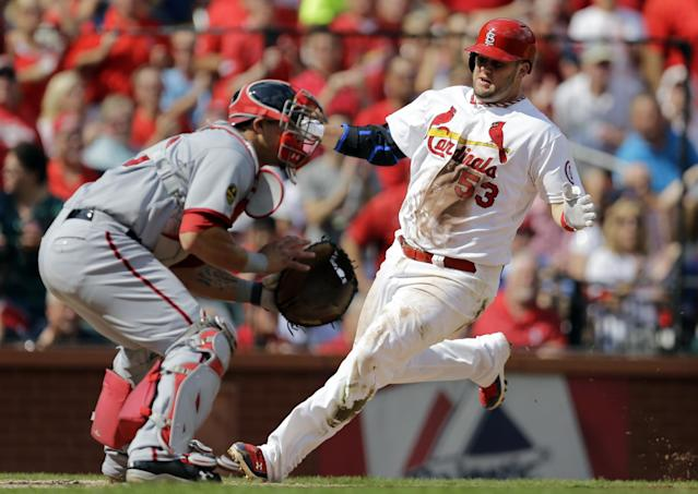 St. Louis Cardinals' Matt Adams, right, scores on a two-run single by St. Louis Cardinals as Washington Nationals catcher Wilson Ramos, left, waits for the throw during the fourth inning of a baseball game Wednesday, Sept. 25, 2013, in St. Louis. (AP Photo/Jeff Roberson)