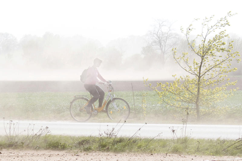 A cyclist makes his way through a heavy storm in Burgdorf, Germany, Tuesday, April 23, 2019. (Julian Stratenschulte/dpa via AP)