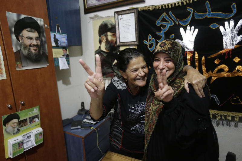 Relatives of nine Lebanese Shiite pilgrims who were kidnapped by a rebel faction in northern Syria in May 2012, flash victory signs as they celebrate news of their relatives release, in the southern suburb of Beirut, Lebanon, Saturday, Oct. 19, 2013. Nine Shiite pilgrims from Lebanon kidnapped in Syria were freed late Friday night as part of a negotiated hostage deal that could see two Turkish pilots held by Lebanese militants released, officials said. The complicated three-way deal also potentially includes the release of female prisoners now held by the embattled government of Syrian President Bashar Assad. (AP Photo/Hussein Malla)