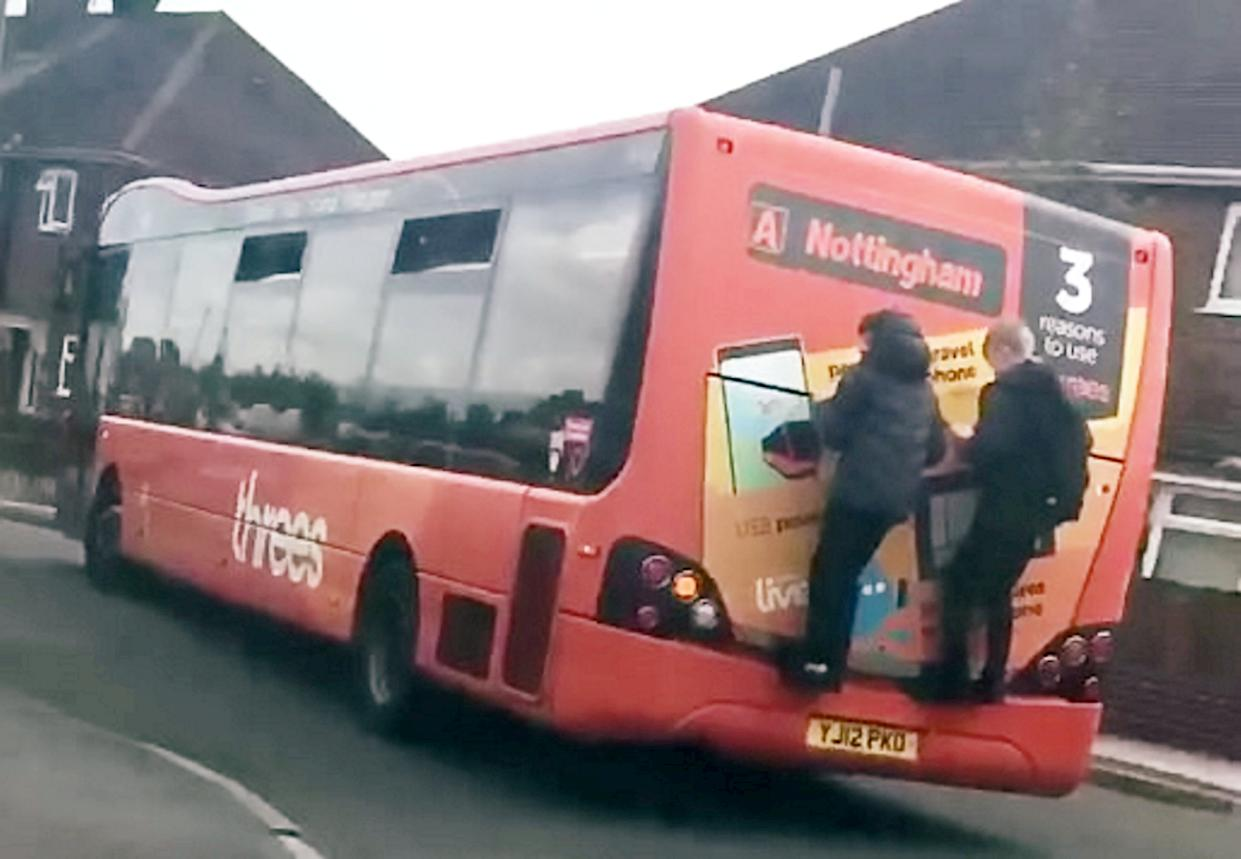 This is the shocking moment two reckless schoolboys hang on to the back of a bus for more than a minute before jumping off. (SWNS)