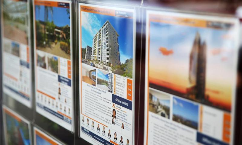 A residential property information leaflet advertising an apartment for sale is displayed in the window of a property agent in Sydney.