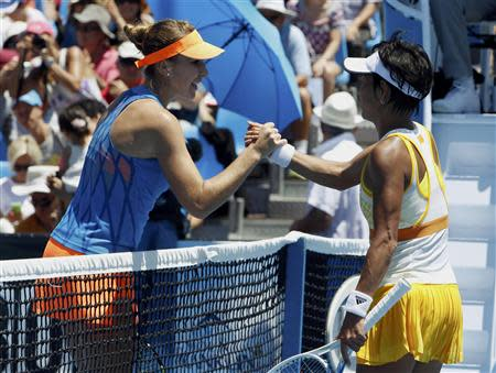 Belinda Bencic (L) of Switzerland clasps hands with Kimiko Date-Krumm of Japan at the net after defeating her in their women's singles match at the Australian Open 2014 tennis tournament in Melbourne January 13, 2014. REUTERS/Brandon Malone