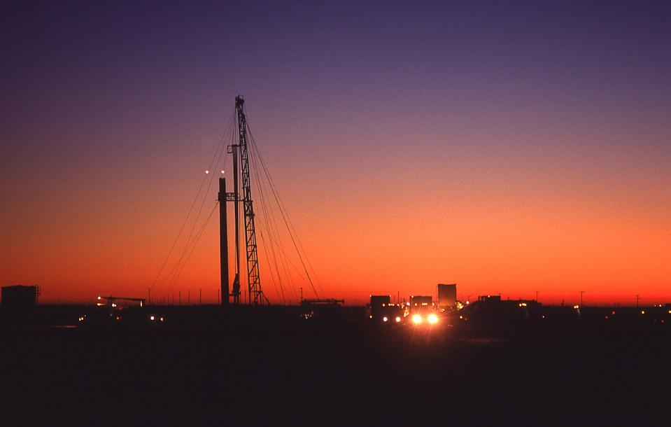 Trucks leaving a drilling site at dusk. (Photo by: Education Images/Universal Images Group via Getty Images)
