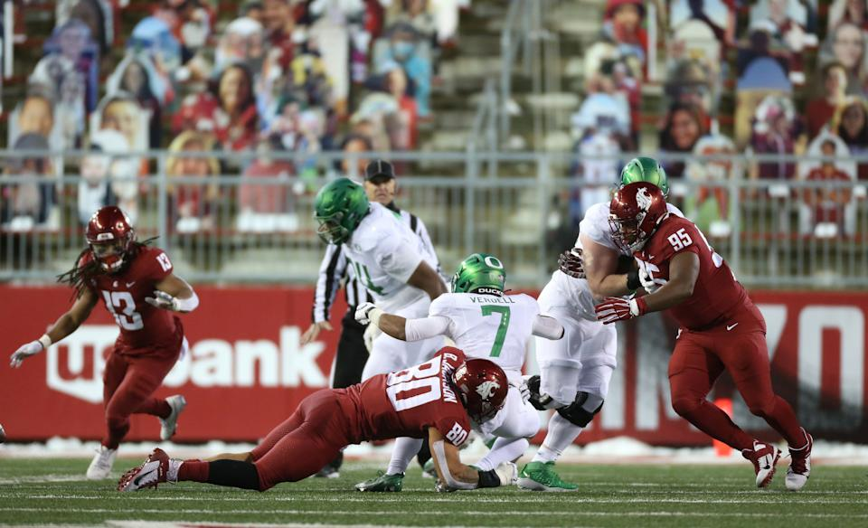 CJ Verdell #7 of the Oregon Ducks is tackled by Brennan Jackson #80 of the Washington State Cougars in the first half at Martin Stadium on Nov. 14. (William Mancebo/Getty Images)