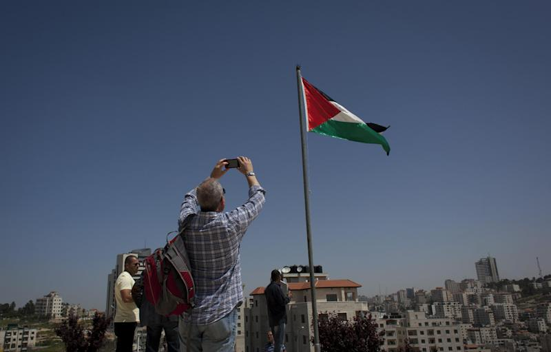 In this photo taken Wednesday, April 16, 2014, a member of the Israeli and foreigner's group tour, that is organized by IPCRI, an Israeli Palestinian group promoting co-existence, takes a photo of the Palestinian national flag during their visit to a museum dedicated to national poet Mahmoud Darwish, at the West Bank city of Ramallah. This bustling center of Palestinian life is just a 20-minute drive from Jerusalem, but for Israelis it might as well be on the other side of the world. (AP Photo/Nasser Nasser)