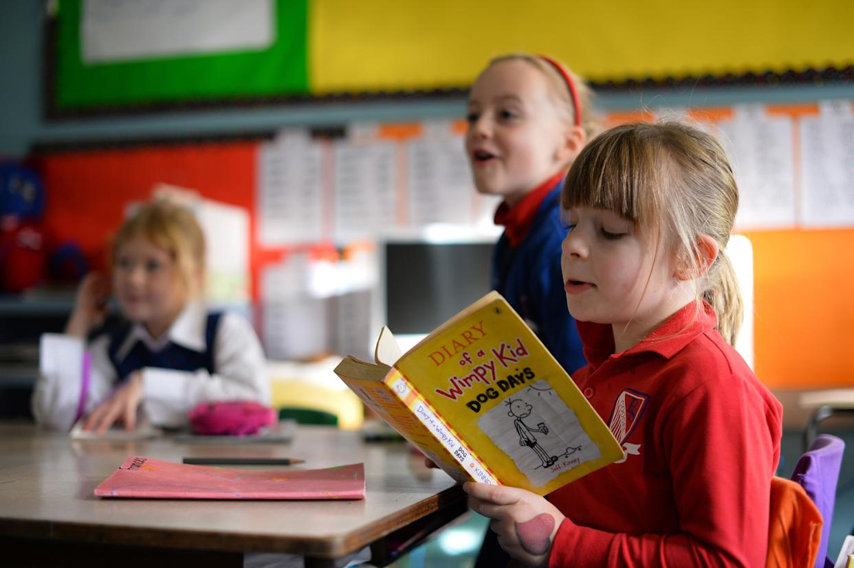 Frances McMillan (right) reads a book inside a classroom at school on June 17, 2013.