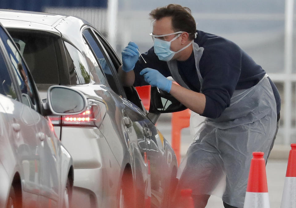 Staff work at a the COVID-19 testing facility at Ikea near the Wembley stadium in London, Wednesday, April 29, 2020. Coronavirus testing is now available for more people in England from Wednesday as the government relaxed rules on eligibility. (AP Photo/Frank Augstein)
