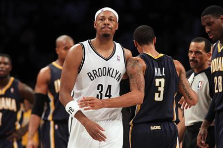 Brooklyn Nets small forward Paul Pierce (34) and Indiana Pacers point guard George Hill (3) walk past one another after Pierce was called for a flagrant foul against Hill during the third quarter of a game at Barclays Center. Brad Penner-USA TODAY Sports