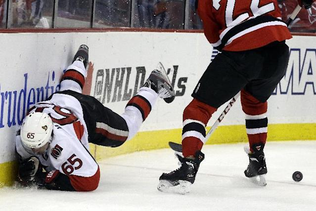 Ottawa Senators defenseman Erik Karlsson (65), of Sweden, falls to the ice while competing for the puck with New Jersey Devils defenseman Eric Gelinas (22) during the first period of an NHL hockey game, Wednesday, Dec. 18, 2013, in Newark, N.J. (AP Photo/Julio Cortez)