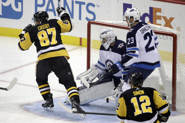 Pittsburgh Penguins center Sidney Crosby (87) celebrates his goal past Winnipeg Jets goaltender Connor Hellebuyck (37) during the first period of an NHL hockey game in Pittsburgh, Tuesday, Oct. 8, 2019. (AP Photo/Gene J. Puskar)
