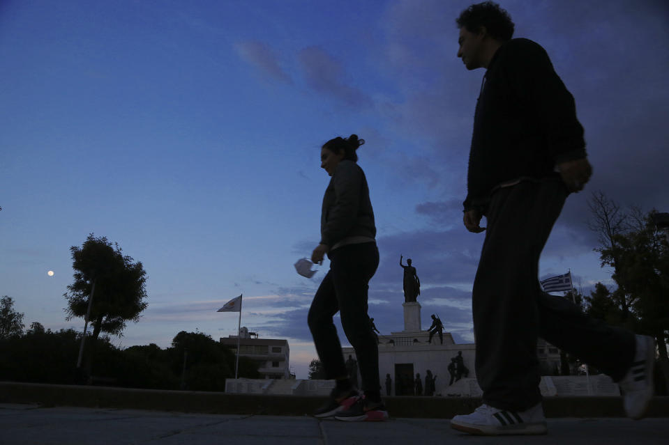 A woman holds a face mask and a man walk in front of the Liberty monument in central capital Nicosia, Cyprus, Wednesday, Jan. 27, 2021. Cyprus' health minister Constantinos Ioannou said that the first to re-open as of Feb. 1st will be hair and beauty salons followed a week later by retail stores, shopping malls and elementary schools. Students in their final year of high school will also go back to classes on Feb. 8. (AP Photo/Petros Karadjias)