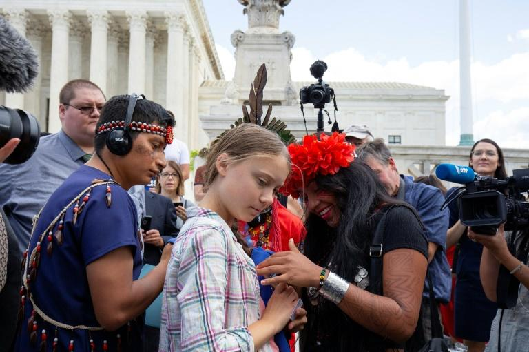Swedish environment activist Greta Thunberg (C) speaks with Militza Flaco (R) from the Global Alliance of Territorial Communities Guardians of the Forest after a gathering outside the US Supreme Court